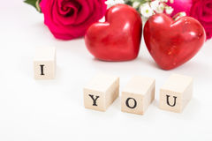 Two red hearts and roses, and wooden cubes with words I and You, on white background. Royalty Free Stock Photos