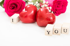 Two red hearts and roses, and wooden cubes with words I and You, on white background. Royalty Free Stock Photo