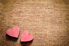 Two red hearts on sackcloth, canvas background. Vintage style. Stock Photos