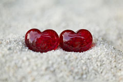 Two red hearts in sand. Symbol of love,two red hearts with stones on the sand Stock Photos