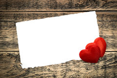Two red hearts. And a sheet of paper on wooden texture Stock Image