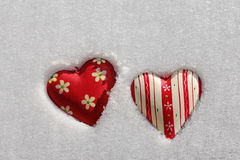 Two red hearts in the snow Royalty Free Stock Photos