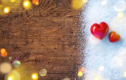 Two red hearts on snow and rustic background. Love and St. Valentines Day concept Stock Photo
