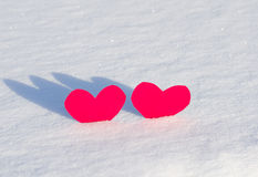 Two red hearts in  snow. On sunlight Royalty Free Stock Image