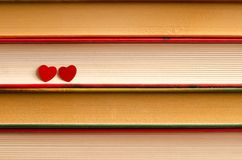 Two hearts on a stack of books close up. Two red hearts on a stack of books close up abstract background Stock Photos