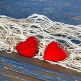 Two red hearts and string on blue wooden surface. Royalty Free Stock Photos