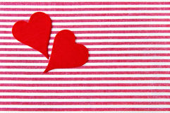 Two red hearts on a striped background. Two red hearts on a striped red-white background Royalty Free Stock Images