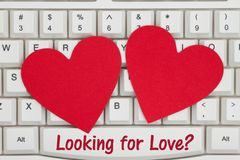 Two red hearts with text Looking for Love on a keyboard royalty free stock photos