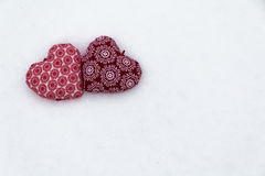 Two  red hearts together in the snow. Symbol of love. Stock Photos