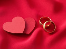 Two red hearts and two wedding rings Royalty Free Stock Image