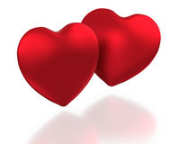 Two red hearts on white background. Two red hearts paired on white background with subdued reflection Royalty Free Stock Photography