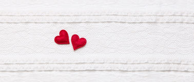 Two red hearts on white lace fabric Royalty Free Stock Photo