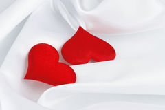 Two red hearts on white silk Stock Photography