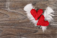 Two Red hearts on wooden background. Two Red hearts with feathers on old wooden background royalty free stock photo