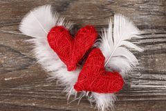 Two Red hearts on wooden background. Two Red hearts with feathers on old wooden background Royalty Free Stock Image