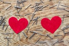 Two red hearts on wooden background surrounded by iron nails. Two red love hearts on wooden background surrounded by iron nails royalty free stock photo
