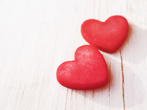 Two red hearts on a wooden white background, soft focus. Romantic card. Stock Image