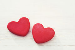 Two red hearts on a wooden white background, soft focus. Romantic card. Royalty Free Stock Photography