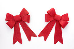 Two red holiday bows angled toward one another Royalty Free Stock Image