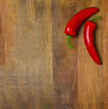 Two red hot chili peppers on a wooden background Royalty Free Stock Photo