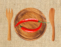 Two red hot chilli peppers on wooden plate over burlap Royalty Free Stock Images