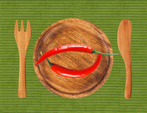 Two red hot chilli peppers on wooden plate over green cloth Royalty Free Stock Image