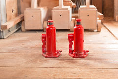 Two red hydraulic car jack on wooden. Small red hydraulic car jack on wooden royalty free stock photos