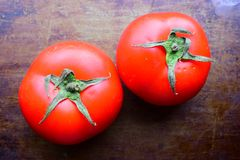 Two Red juicy tomato on a dark old brown background Royalty Free Stock Images
