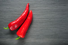 Two red Kapia peppers on a dark shale stone background Royalty Free Stock Photography