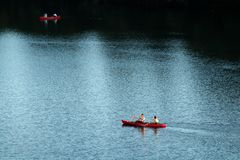 Two red kayaks navigating light and dark waters of Colorado river as seen from Congress bridge in Austin stock photos