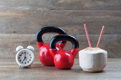 Two red kettlebells with coconut and clock on walnut wood Stock Photo
