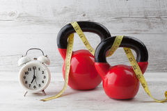 Two red kettlebells with measuring tape and clock Royalty Free Stock Photo