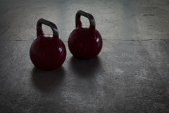 Two red kettlebells on a stone floor in a gym - background light Royalty Free Stock Photo