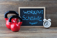 Two red kettlebells with vintage clock and blackboard. Royalty Free Stock Photos