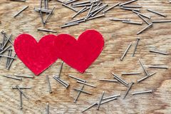 Two red hearts on wooden background surrounded by iron nails. Two red love hearts on wooden background surrounded by iron nails stock photos