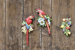 Two red macao parrots clay figures on on the. Colorful clay parrots on a rustic wooden backgorund stock photos