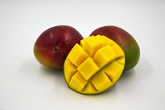 Ripe Mangoes. Two red mangoes with a half mango slice cut into cubes Royalty Free Stock Photography