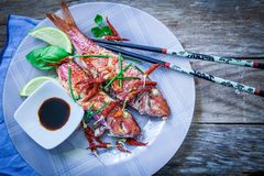 Red mullet fish style. Two red mullet with chili pepper and soja sauce on plate with chopstick Royalty Free Stock Photography