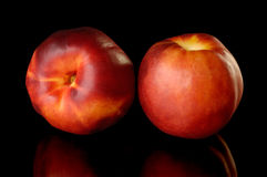 Two red nectarine peaches. Isolated on black background Royalty Free Stock Photo