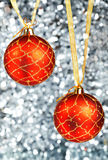 Two red New Year's balls hang on gold ribbons Stock Images