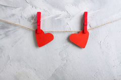 Two red paper hearts hanging onto clothespins on a rope. Royalty Free Stock Image