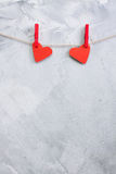Two red paper hearts hanging onto clothespins on a rope. Stock Photos