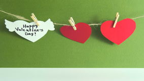 Two red paper hearts and one white heart with congratulation and wings fixed with clothespins on a cord on green stock video footage