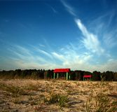Two red pavilions. Two red pavilions on sandy waste ground near to lake Royalty Free Stock Image