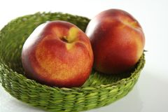 Two red peaches in a green basket. Summer fruits, two red peaches in a green basket royalty free stock images