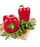 Two red peppers. And parsley on a cutting board, isolated on white background Royalty Free Stock Photography
