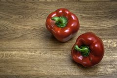 Two red peppers on a brown wooden table royalty free stock photography