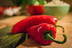 Two red peppers lying on a wooden table.  stock photography