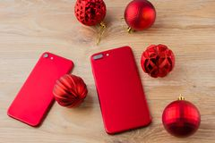 Two red phones and Christmas balls. Smartphones of red color lie on a wooden table next to Christmas balls Royalty Free Stock Photography