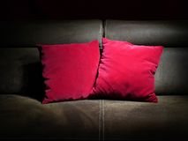 Two red pillows. On brown leather sofa Stock Photos
